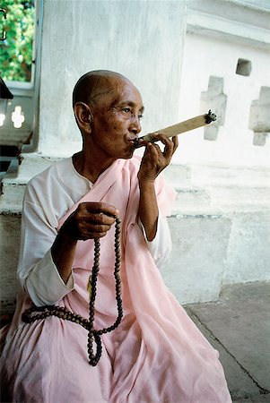 Myanmar, Mandalay area, Nun smoking cigar while holding prayer beads Stock Photo - Rights-Managed, Code: 849-02866298