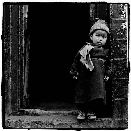 India, Ladakh, Portrait of little boy standing in doorway. Stock Photo - Rights-Managed, Code: 849-02867562