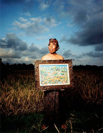 Indonesia, Bali, Ubud, Balinese artist holding painting in rice field. Stock Photo - Rights-Managed, Code: 849-02867615