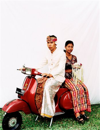 Indonesia, Bali, Ubud, Balinese wedding couple in ceremonial dress, sitting on motor scooter, woman carrying offering. Stock Photo - Rights-Managed, Code: 849-02867618