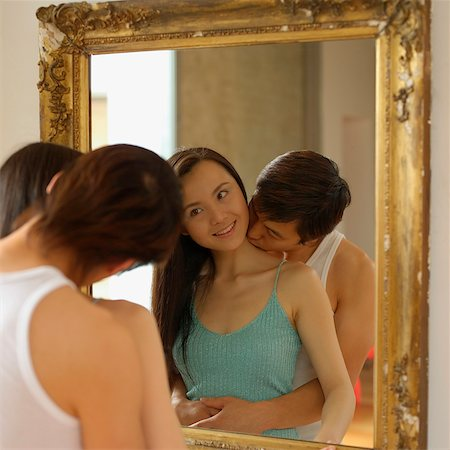 Woman looking at mirror, man kissing her neck Stock Photo - Rights-Managed, Code: 849-02868487