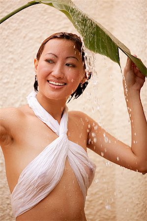 Young woman holding leaf, water cascading on her, looking away Stock Photo - Rights-Managed, Code: 849-02868823
