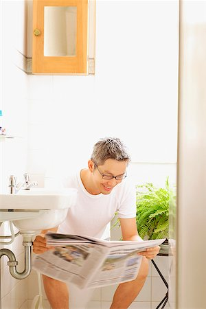 Man on toilet, reading newspaper Stock Photo - Rights-Managed, Code: 849-02869660