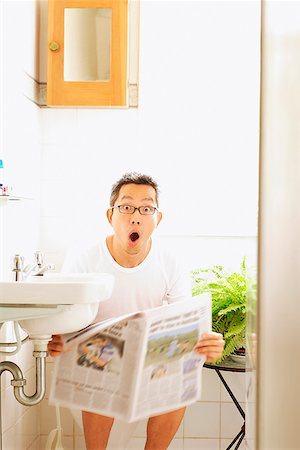 Man on toilet, holding newspaper, mouth open Stock Photo - Rights-Managed, Code: 849-02869661