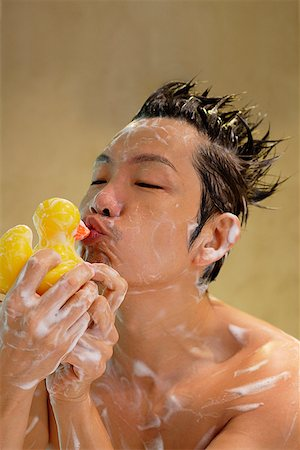 A man covered in soap suds plays with a rubber duck Stock Photo - Rights-Managed, Code: 849-02860912