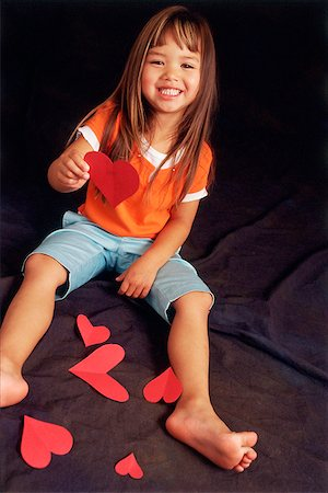 Young girl holding paper hearts, looking at camera Stock Photo - Rights-Managed, Code: 849-02870611