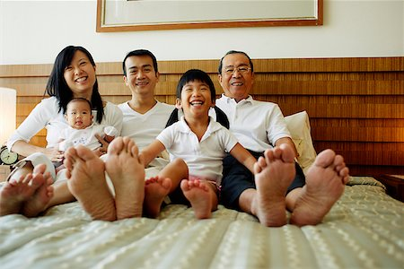 Three generation family on bed, looking at camera, low angle view Stock Photo - Rights-Managed, Code: 849-02871165