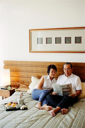 Older couple lying on bed, reading newspaper Stock Photo - Rights-Managed, Code: 849-02871174