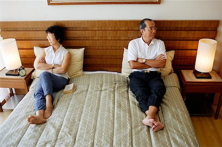 sad lovers break up - Older couple lying apart on bed, arms crossed Stock Photo - Rights-Managed, Code: 849-02871180