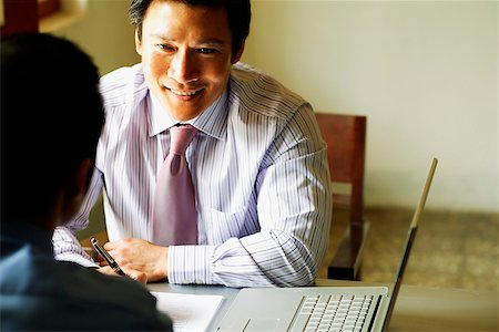 dependable - Businessmen talking, laptop open next to them Stock Photo - Rights-Managed, Code: 849-02871381