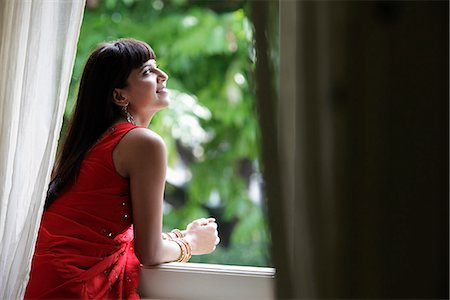 singapore traditional costume lady - Indian woman looking out window, smiling Stock Photo - Rights-Managed, Code: 849-03645373