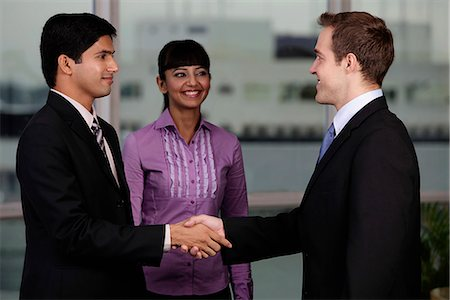 Indian and Caucasian man shaking hands while woman looks on. Stock Photo - Rights-Managed, Code: 849-03645448