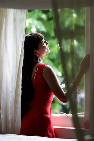 singapore traditional costume lady - Indian woman looking out window smiling Stock Photo - Rights-Managed, Code: 849-03645469