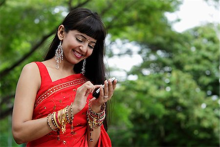 singapore traditional costume lady - Indian woman texting on phone, outdoors Stock Photo - Rights-Managed, Code: 849-03645660