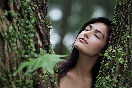 Head shot of young woman resting her head on a tree with eyes closed. Stock Photo - Rights-Managed, Code: 849-03645685