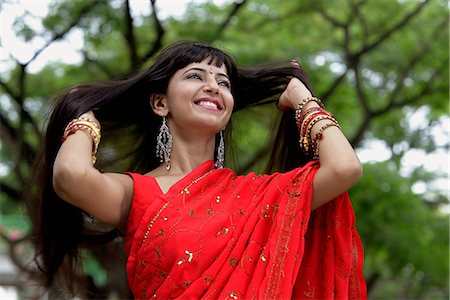 singapore traditional costume lady - Indian woman wearing red sari smiling with hands in hair Stock Photo - Rights-Managed, Code: 849-03645706