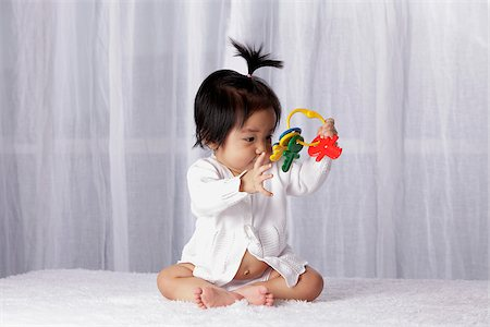 Chinese baby looking at toy key ring Stock Photo - Rights-Managed, Code: 849-03775969