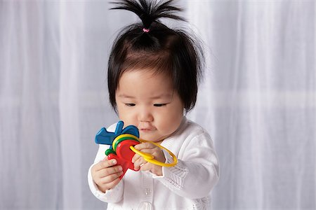 Chinese baby holding toy key ring Stock Photo - Rights-Managed, Code: 849-03775986