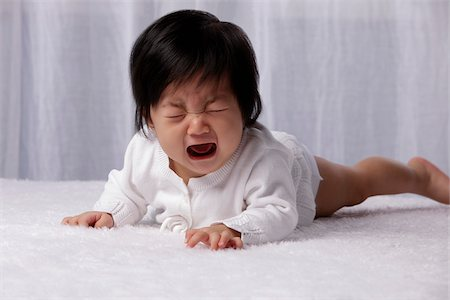 sad girls - Chinese baby on tummy crying Stock Photo - Rights-Managed, Code: 849-03776003