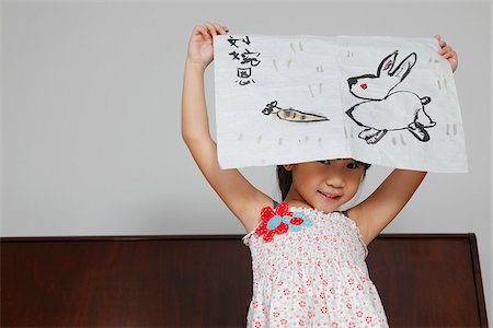 showing - Young Chinese girl smiling holding up picture of rabbit Stock Photo - Rights-Managed, Code: 849-03901142