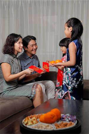singapore traditional costume lady - Chinese parents giving red envelopes (Hong Bao) to daughters during Chinese New Year Stock Photo - Rights-Managed, Code: 849-03901160