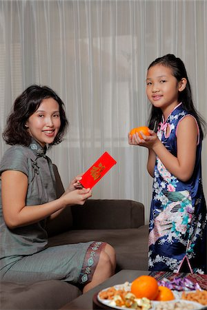 singapore traditional costume lady - Mother giving daughter a red envelope (Hong Bao) during Chinese New Year Stock Photo - Rights-Managed, Code: 849-03901227