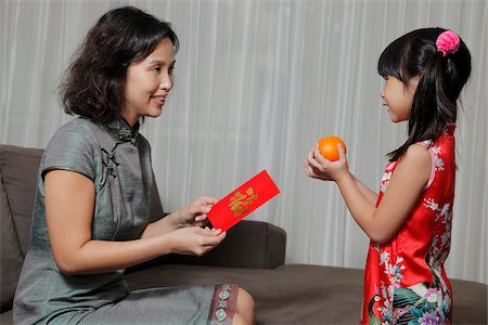singapore traditional costume lady - Mother giving daughter a red envelope(Hong Bao) while daughter gives two oranges Stock Photo - Rights-Managed, Code: 849-03901231