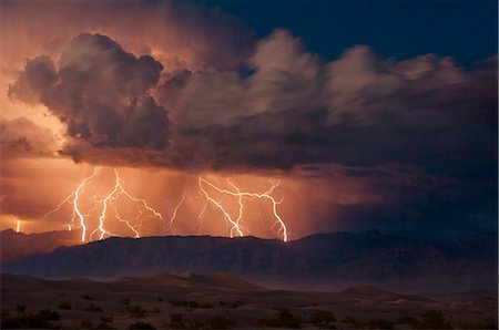 Electrical storm with forked lightning over the Grapevine mountains of the Amargosa Range, Mesquite Flats Sand dunes in the valley, Stovepipe Wells, Death Valley National Park, California, United States of America, North America Stock Photo - Rights-Managed, Code: 841-05782326