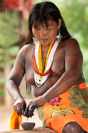 panama traditional costume - Embera woman, dressed in traditional print skirt and beads with jagua tattoo on her upper body, extracting the juice of a jagua nut used to apply tattoos, Embera Drua Village, Chagres River, Soberania National Park, Panama, Central America Stock Photo - Rights-Managed, Code: 841-05797067