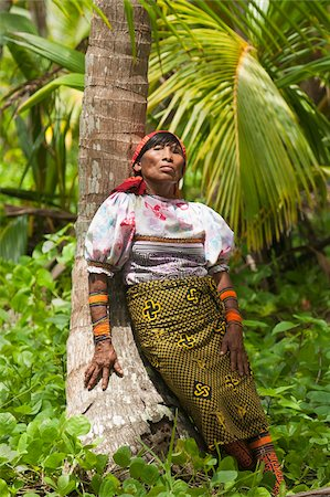 panama traditional costume - Kuna Indian woman in print skirt and mola blouse rests against a palm tree on a deserted tropical island in Kuna Yala (San Blas Islands), Caribbean coast of northern Panama, Central America Stock Photo - Rights-Managed, Code: 841-05797071