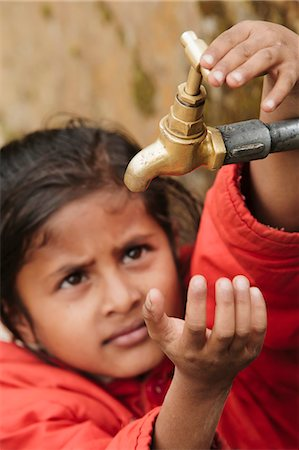 Young girl checking to see if the communal village water tap has water, as it runs dry daily, Pokhara, Nepal, Asia Stock Photo - Rights-Managed, Code: 841-06030827