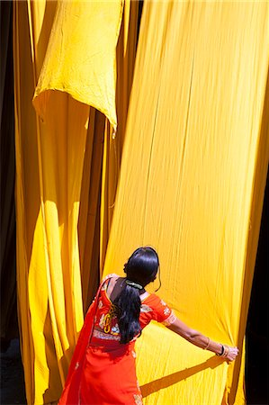 Woman in sari checking the quality of freshly dyed fabric hanging to dry, Sari garment factory, Rajasthan, India, Asia Stock Photo - Rights-Managed, Code: 841-06031278