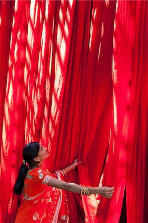 Woman in sari checking the quality of freshly dyed fabric hanging to dry, Sari garment factory, Rajasthan, India, Asia Stock Photo - Rights-Managed, Code: 841-06031279