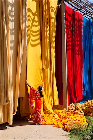 Woman in sari checking the quality of freshly dyed fabric hanging to dry, Sari garment factory, Rajasthan, India, Asia Stock Photo - Rights-Managed, Code: 841-06031281