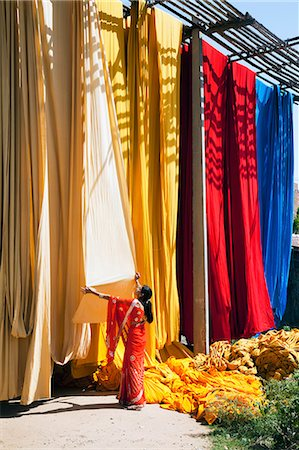 Woman in sari checking the quality of freshly dyed fabric hanging to dry, Sari garment factory, Rajasthan, India, Asia Stock Photo - Rights-Managed, Code: 841-06031283