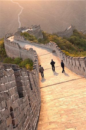 Three men walking on Great Wall of China, UNESCO World Heritage Site, Huanghua Cheng (Yellow Flower) at sunset, Xishulyu, Jiuduhe Zhen, Huairou, China, Asia Stock Photo - Rights-Managed, Code: 841-06033075