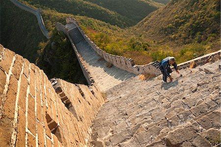 Chinese man climbs Great Wall of China, UNESCO World Heritage Site, Huanghuacheng (Yellow Flower) at sunset in autumn, Jiuduhe Zhen, Huairou, China, Asia Stock Photo - Rights-Managed, Code: 841-06033073