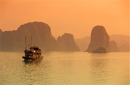Traditional boat sailing through limestone archipelago at sunset, Ha Long Bay, UNESCO World Heritage Site, Northeast, Vietnam, Indochina, Southeast Asia, Asia Stock Photo - Rights-Managed, Code: 841-06033291