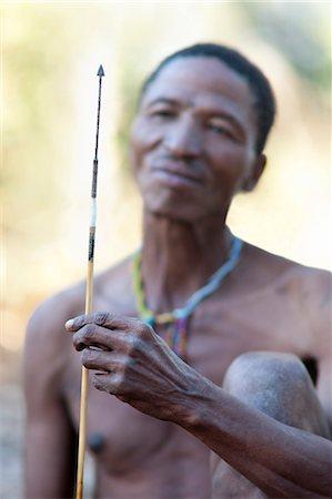 Jul'hoan !Kung Bushman on a hunter-gatherer expedition admiring his sharpened arrow, Kalahari Desert, Namibia, Africa Stock Photo - Rights-Managed, Code: 841-06344727