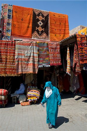 A woman in traditional Islamic dress walking past carpets hanging around an entrance to the souk in Marrakech, Morocco, North Africa, Africa Stock Photo - Rights-Managed, Code: 841-06445540