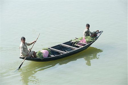 Village men punting a wooden boat along the River Hugli (River Hooghly), carrying bundles of alfalfa to market, near Kolkata, West Bengal, India, Asia Stock Photo - Rights-Managed, Code: 841-06447694