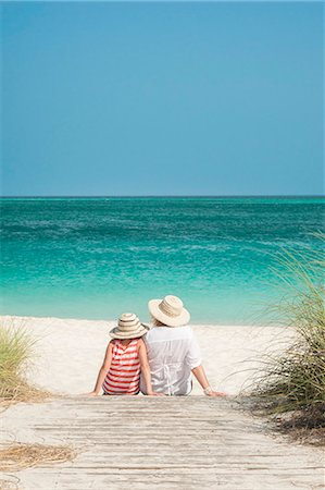 Mother and daughter sitting on boardwalk facing ocean, Grace Bay Beach, Providenciales, Turks and Caicos Islands, West Indies, Caribbean, Central America Stock Photo - Rights-Managed, Code: 841-06448701