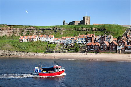 Fishing boat entering the harbour below Whitby Abbey, Whitby, North Yorkshire, Yorkshire, England, United Kingdom, Europe Stock Photo - Rights-Managed, Code: 841-06449087