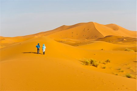 Two Berber men walking in the sand dunes of Erg Chebbi Desert, Sahara Desert near Merzouga, Morocco, North Africa, Africa Stock Photo - Rights-Managed, Code: 841-06804624