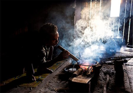 smoke - Man of the Palaung tribe cooking on open fire in his home in village near Kengtung (Kyaingtong), Shan State, Myanmar (Burma), Asia Stock Photo - Rights-Managed, Code: 841-06805767