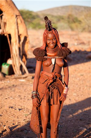 Young Himba woman wearing traditional dress and jewellery and with her skin covered in Otjize, a mixture of butterfat and ochre, Kunene Region, formerly Kaokoland, Namibia, Africa Stock Photo - Rights-Managed, Code: 841-06805770