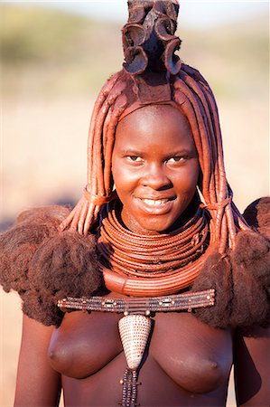 Young Himba woman wearing traditional dress and jewellery and with her skin covered in Otjize, a mixture of butterfat and ochre, Kunene Region, formerly Kaokoland, Namibia, Africa Stock Photo - Rights-Managed, Code: 841-06805771