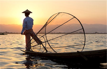 Intha 'leg rowing' fishermen at sunset on Inle Lake who row traditional wooden boats using their leg and fish using nets stretched over conical bamboo frames, Inle Lake, Myanmar (Burma), Southeast Asia Stock Photo - Rights-Managed, Code: 841-07081659