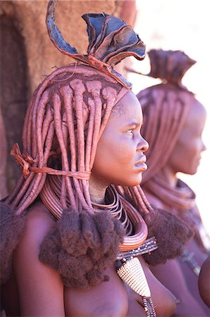 Young Himba woman wearing traditional dress and jewellery and with her skin covered in Otjize, a mixture of butterfat and ochre, Kunene Region, formerly Kaokoland, Namibia Stock Photo - Rights-Managed, Code: 841-07081785