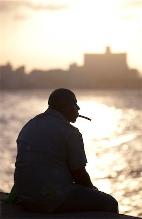 Man in semi silhouette sat on the sea wall at sunset, smoking a cigar, The Malecon, Havana Centro, Havana, Cuba, West Indies, Central America Stock Photo - Rights-Managed, Code: 841-07081809